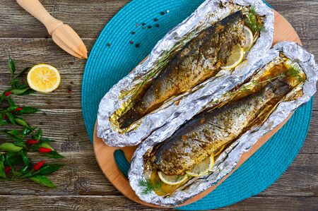 Baked herring with lemon and spices in foil on a wooden table. Tasty fish dish. Top view. Stock fotó