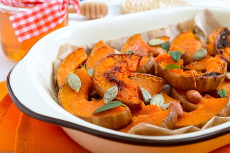 Pumpkin slices baked in the oven with honey, nuts, cinnamon, seeds, mint. Pieces of pumpkin lying on the baking paper in a bowl. Healthy food, dessert for gourmets. Traditional autumn snack