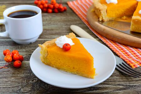 Piece of traditional homemade pumpkin pie and a cup of coffee on a wooden table. Healthy food, dessert for gourmets. Thanksgiving theme. Traditional autumn baking.