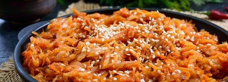 Braised cabbage from tomato sauce in a cast-iron frying pan on a black background. Lenten menu. Diet low-calorie vegetable dish. Banner