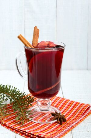 Hot mulled wine in a glass on a white wooden background. A traditional warming winter wine drink with aromatic spices. Vertical view.
