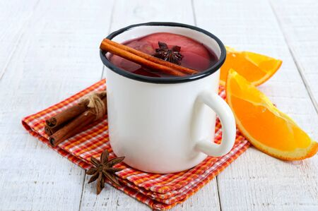 Hot mulled wine in a mug on a white wooden background. A traditional warming winter wine drink with aromatic spices.