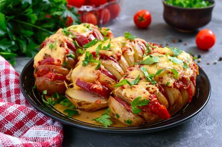 Hasselback potato stuffed with salami, cheese, ketchup, garlic and herbs. Baked whole potatoes is sliced and stuffed. Traditional swedish recipe.