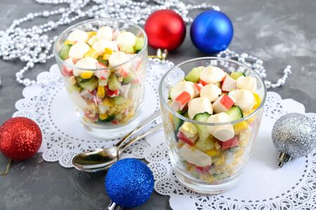 Crab salad. Delicious light salad of crab sticks, corn, fresh cucumbers, eggs in a glass cup. Holiday salad. Dishes for the New Year, Christmas