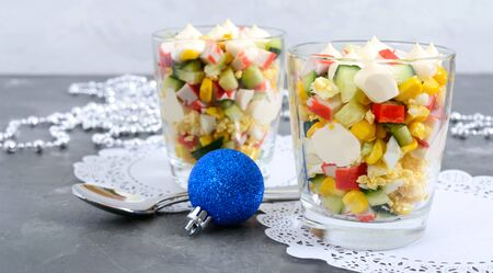 Crab salad. Delicious light salad of crab sticks, corn, fresh cucumbers, eggs in a glass cup. Holiday salad. Dishes for the New Year, Christmas.