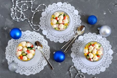 Crab salad. Delicious light salad of crab sticks, corn, fresh cucumbers, eggs in a glass cup. Holiday salad. Dishes for the New Year, Christmas. Top view. Banco de Imagens