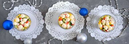 Crab salad. Delicious light salad of crab sticks, corn, fresh cucumbers, eggs in a glass cup. Holiday salad. Dishes for the New Year, Christmas. Top view. Banner Banco de Imagens