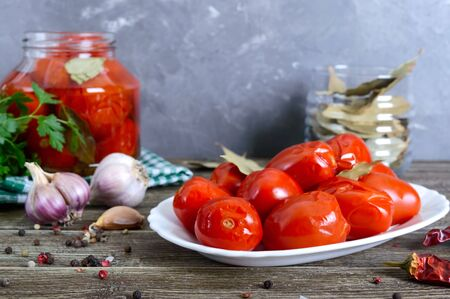Juicy spicy marinated tomatoes with pepper and garlic on a white plate on a wooden table. Homemade canning. Pickled Vegetables.