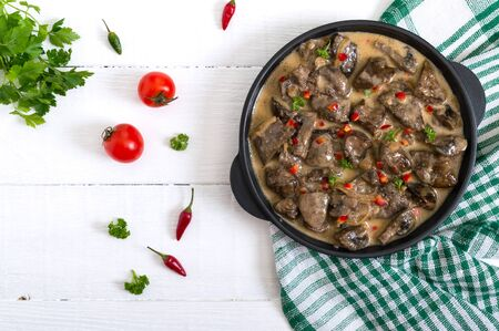 Turkey liver with onions and mushrooms in a creamy sauce on a white wooden background. Diet menu. Top view.
