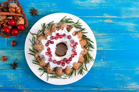 Christmas fruit cake on white plate. Homemade fruitcake decorated with rosemary, powdered sugar and lingonberry on a blue wooden rustic background. The top view