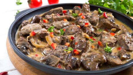 Turkey liver with onions and mushrooms in a creamy sauce on a white wooden background. Diet menu Zdjęcie Seryjne