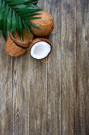 Coconut Whole coconut, shell from coconut and green leaves on a wooden background. Big nut. Tropical fruit coconut in the shell. SPA Food photo. Photo background. Texture tropical fruit. Copy spase