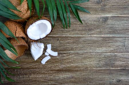 Coconut Whole coconut, shell, coconut flakes and green leaves on a wooden background. Big nut. Tropical fruit coconut in the shell. SPA Food photo. Photo background. Texture tropical fruit.