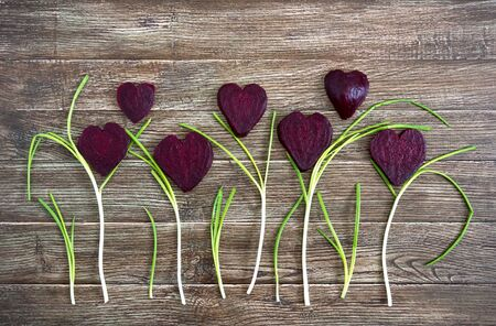 Flowers of sliced boiled beets and green onions on a wooden background. To love beets. Healthy eating concept.