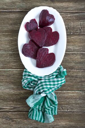 Slices of cooked beets in the shape of a heart on a white plate and a green kitchen towel on a wooden background. To love beets.