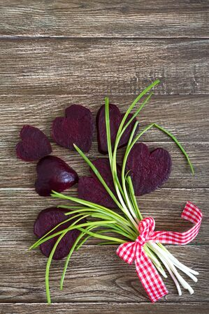 A bouquet of flowers from slices of boiled beets and green onions on a wooden background. To love beets. Healthy eating concept. Happy Valentines Day. Copy space