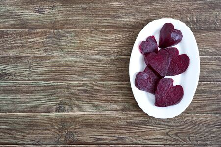 Slices of cooked beets in the shape of a heart on a white plate on a wooden background. To love beets. Copy spase