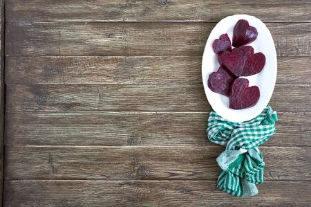 Slices of cooked beets in the shape of a heart on a white plate and a green kitchen towel on a wooden background. To love beets. Copy space
