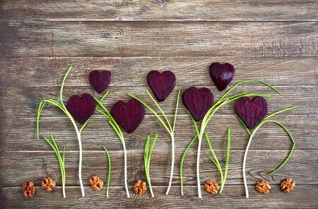 Flowers of sliced boiled beets, walnuts and green onions on a wooden background. To love beets. Healthy eating concept.