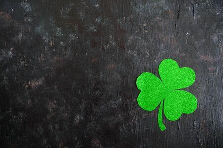 Trèfle vert sur fond noir. Contexte de la Saint-Patrick. Symbole de l'Irlande. Espace de copie. Banque d'images