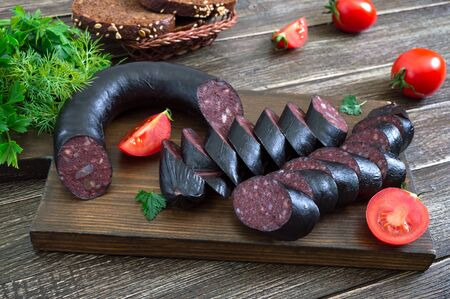 Morsilla - blood sausage. Pieces of Spanish black pudding on a wooden cutting board. Easter menu.