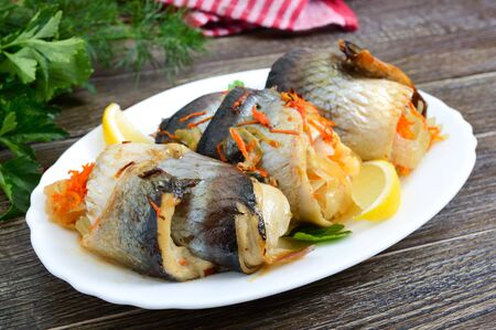 Baked herring stuffed with vegetables. Tasty fish rolls.