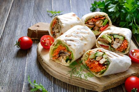 Fresh tortilla wraps with chicken, mushrooms and fresh vegetables on wooden board. Chicken Mexican burrito. Tasty appetizer. Dishes from pita bread. Healthy food concept.
