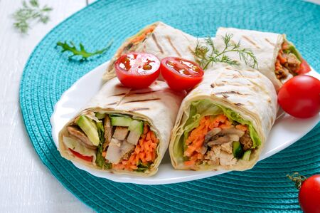 Fresh tortilla wraps with chicken, mushrooms and fresh vegetables. Chicken Mexican burrito. Tasty appetizer. Dishes from pita bread. Healthy food concept Reklamní fotografie