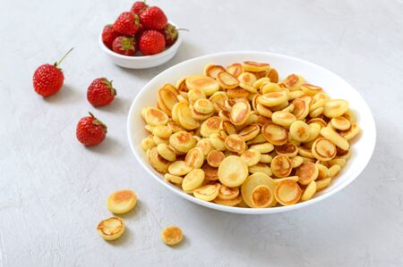 Pancake cereal in a bowl with fresh strawberries on a light background. Tasty and trendy breakfast. Organic Dutch Mini-Pancakes. Foods trend Reklamní fotografie