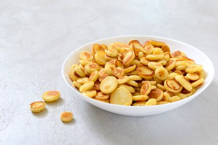 Pancake cereal in a bowl on a light background. Tasty and trendy breakfast. Organic Dutch Mini-Pancakes. Foods trend.