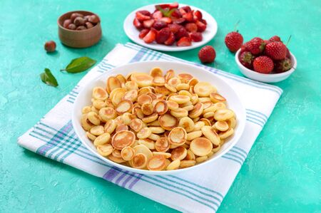 Pancake cereal in a bowl with fresh strawberries and nuts on a bright background. Tasty and trendy breakfast. Organic Dutch Mini-Pancakes. Foods trend. Reklamní fotografie