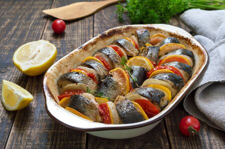 Baked fish with vegetables. Pieces of herring, onions, tomato, lemon, aromatic herbs in ceramic form on a rustic wooden table
