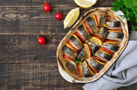 Baked fish with vegetables. Pieces of herring, onions, tomato, lemon, aromatic herbs in ceramic form on a rustic wooden table. Top view.