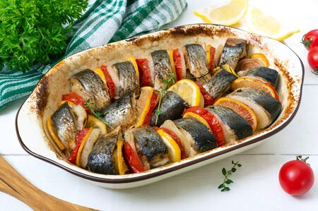 Baked fish with vegetables. Pieces of herring, onion, tomato, lemon, aromatic herbs