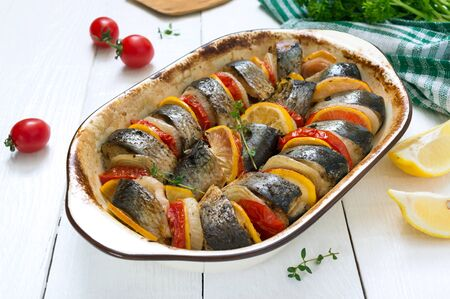 Baked fish with vegetables. Pieces of herring, onion, tomato, lemon, aromatic herbs in ceramic form. Top view.