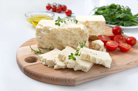 Tasty healthy sheep or goat feta cheese. Chunks of cheese on a wooden board on white background. Stockfoto