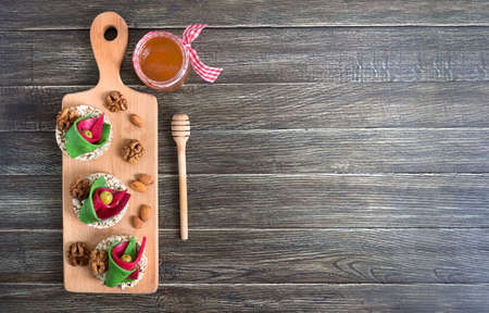 Tasty and healthy canapes with craft cheese, olives, nuts and whole grain bread on a board. Original party snacks. Copy space Stock Photo