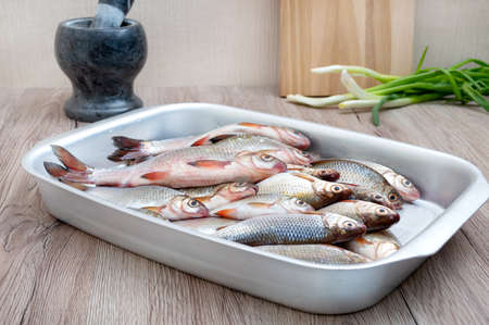 Fresh catch of river fish in a bowl on the table. Healthy food concept. Proper nutrition.