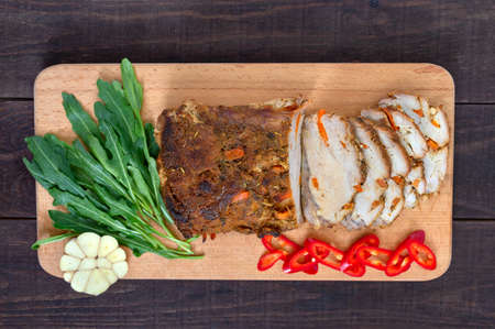 Baked pork brisket, served on a board with fresh arugula and bell peppers. Top view, flat lay Stock Photo