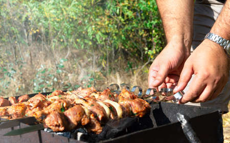 Man cooking marinated shashlik. Meat grilling on metal skewer, close up. Copy space.