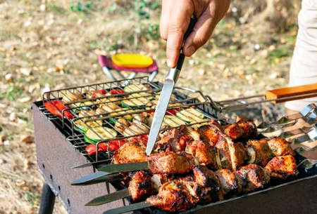 Grilled vegetables and meat on skewers an open fire. Man checks the cooked meat, close-up hands