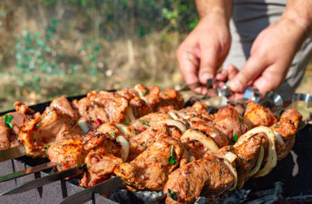 Man prepare juicy slices of meat with sauce on open fire. Grilling a barbecue outdoors.