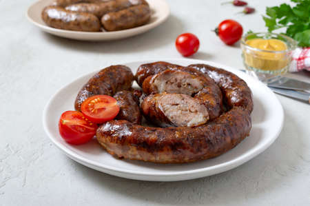 Juicy homemade baked sausage on a plate with mustard and fresh tomatoes. Stock Photo