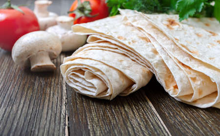 Thin pita bread with fresh vegetables on a wooden background. Lavash - tasty hearty healthy Armenian and Turkish unleavened flat bread. Copy spase Stock Photo