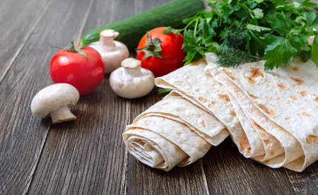 Thin lavash on wooden background with fresh vegetables. Armenian pita bread - unleavened flat bread. Copy spase
