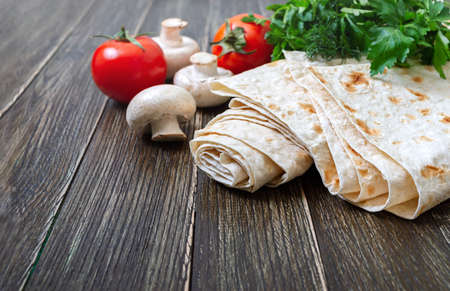 Lavash - tasty hearty healthy Armenian and Turkish unleavened flat bread. Thin lavash on wooden background with fresh vegetables.Copy spase Stock Photo