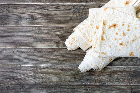 Armenian flat bread lavash. Thin pita bread on wooden background. Top view. Copy space.