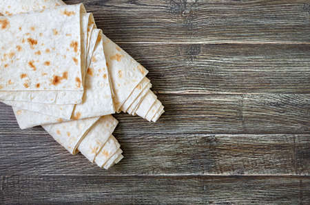 Thin pita bread on wooden background. Lavash - tasty hearty healthy Armenian and Turkish unleavened flat bread. Top view. Copy space. Food background