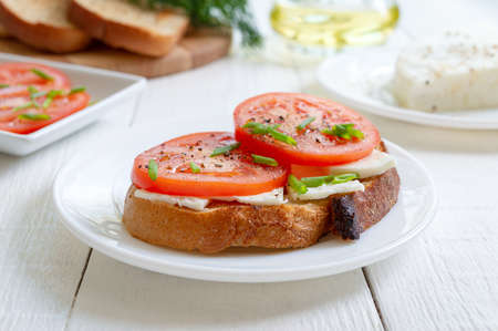 Whole grain bread with goat cheese and fresh tomatoes on white. Healthy and tasty breakfast.