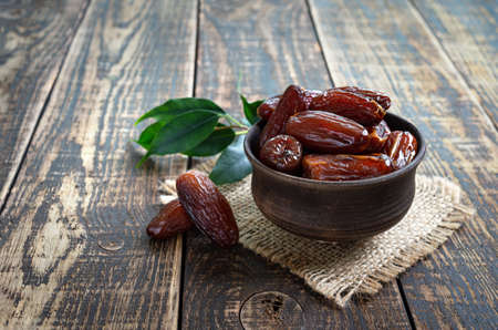 Dried dates fruit in ceramic bowl on old wooden table. Highly valuable food product. Dried fruits.